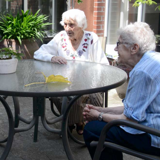 Ross Place Our Story Our Values Card Seniors Enjoying the Courtyard