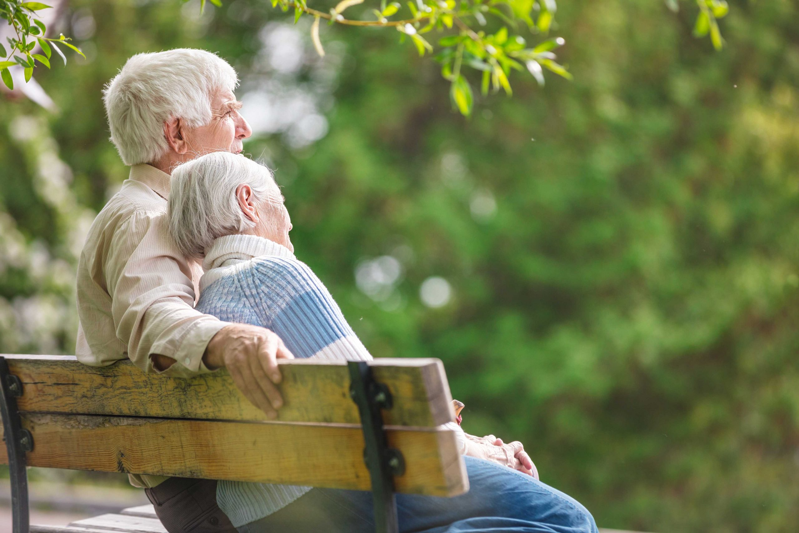 Seniors couple sitting on bench outside