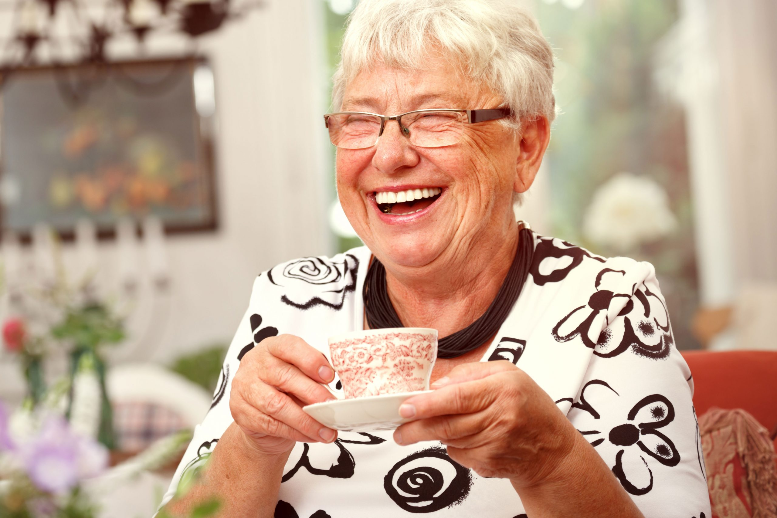 Happy senior woman with tea cup in hand