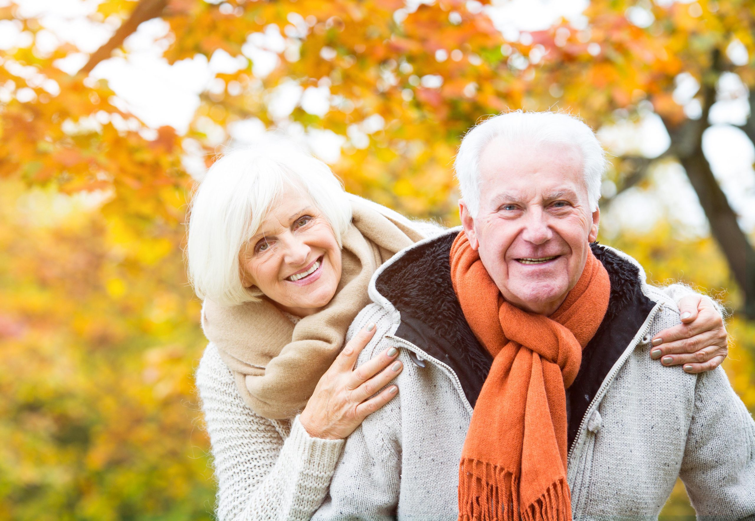 Happy senior couple outside with Autumn trees in the background