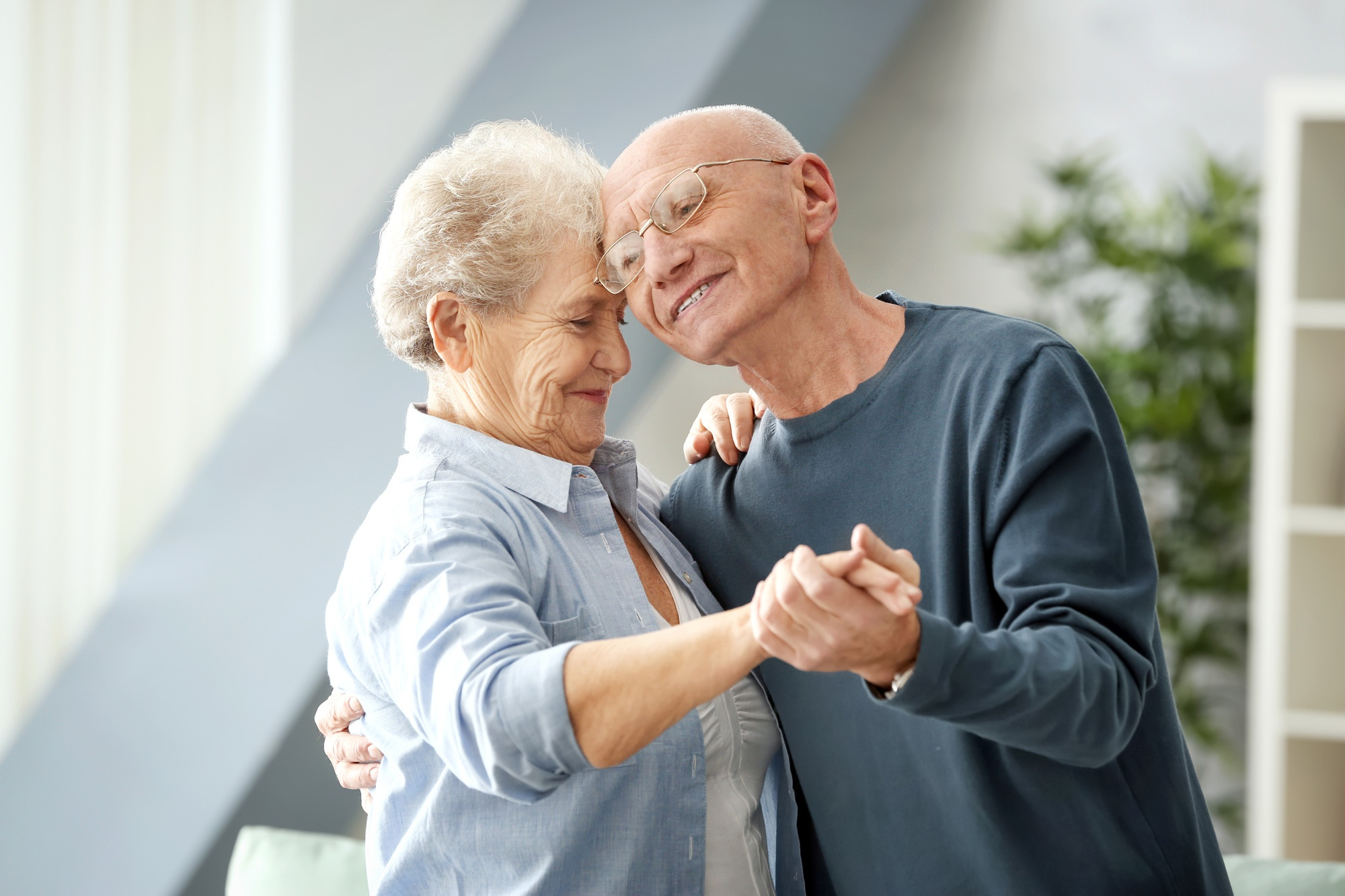 Happy, smiling, seniors couple dancing in living room