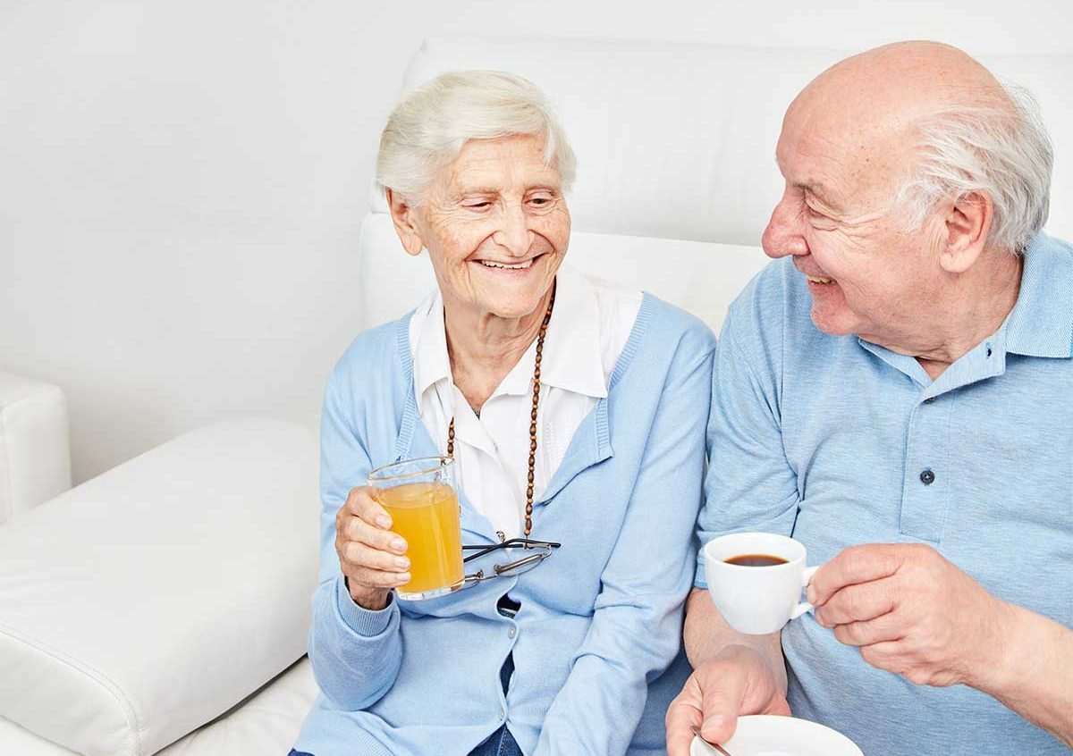 Happy, smiling senior couple sitting on the couch enjoying coffee and juice